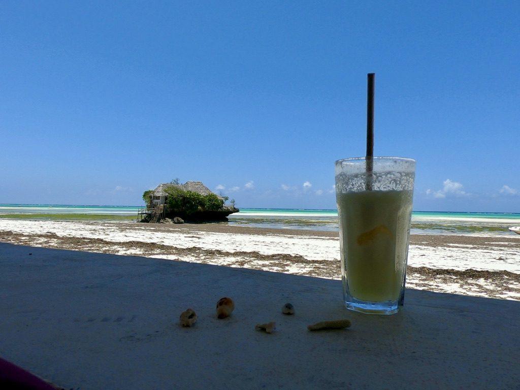 Il ristorante The Rock Zanzibar durante la bassa marea con in primo piano un cocktail da Upendo