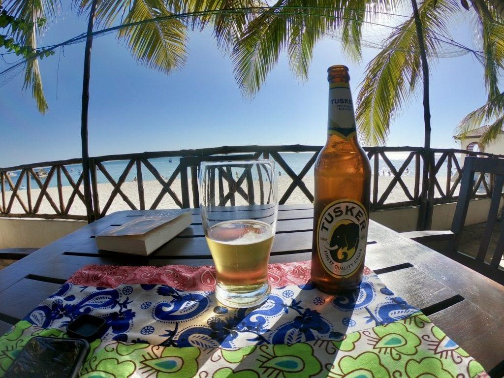 Una bottiglia e un bicchiere su un tavolo in spiaggia a Stone Town