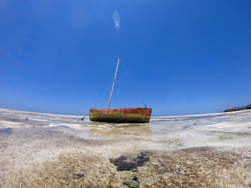 Una barca arenata durante la bassa marea a Zanzibar