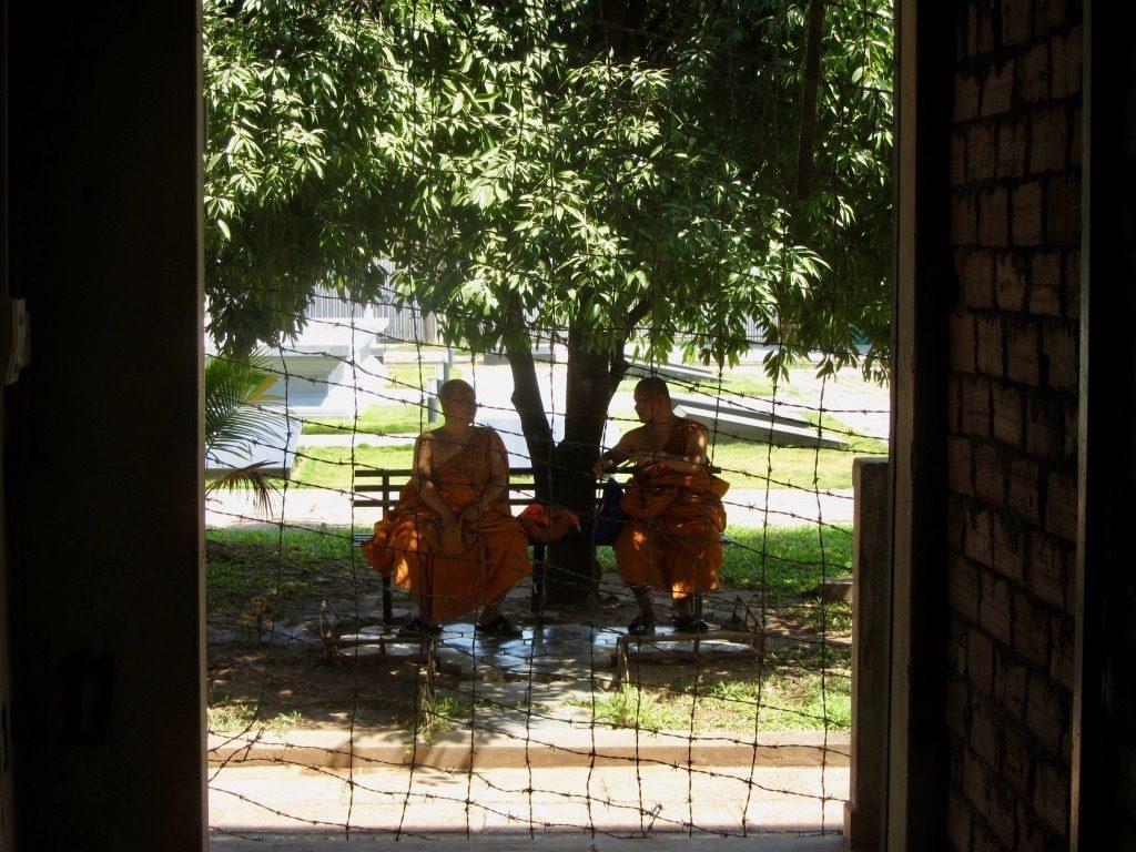 Due monaci si riposano nel cortile di Tuol Sleng durante una visita