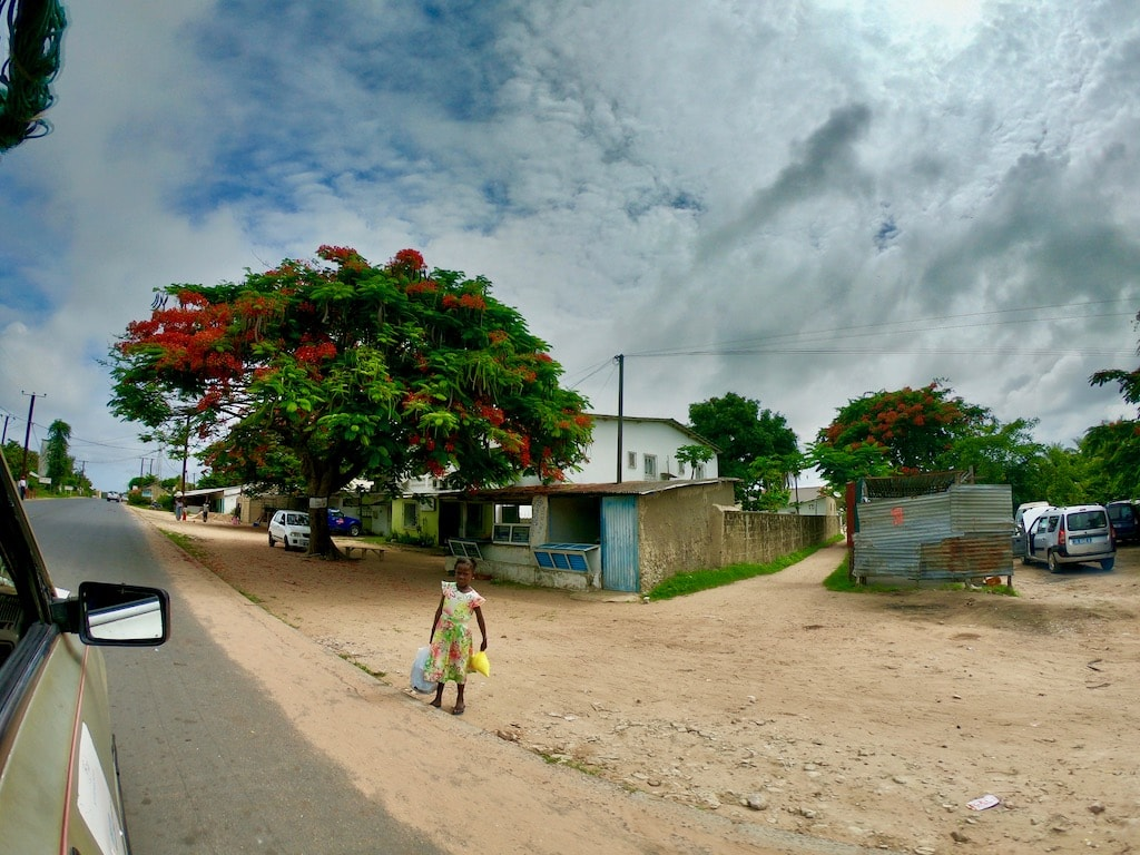 Una strada di Ziguinchor in Casamance con una bambina sul bordo della via