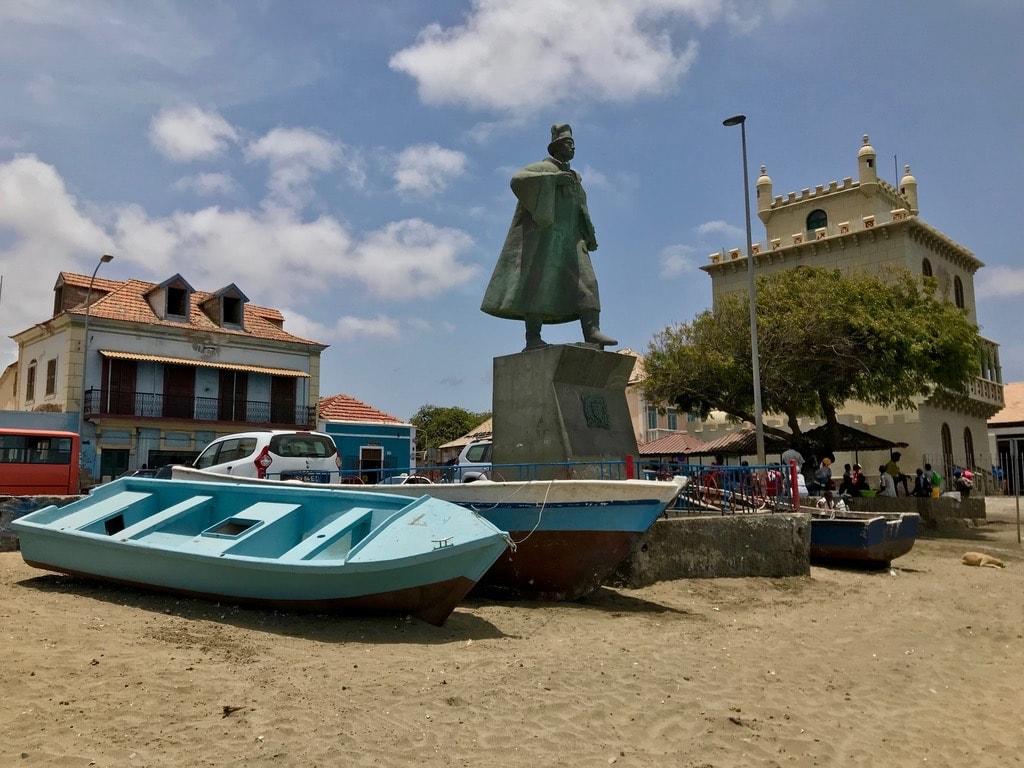 La statua di Diogo Afonso sulla spiaggia di Mindelo con la Torre di Belem sullo sfondo