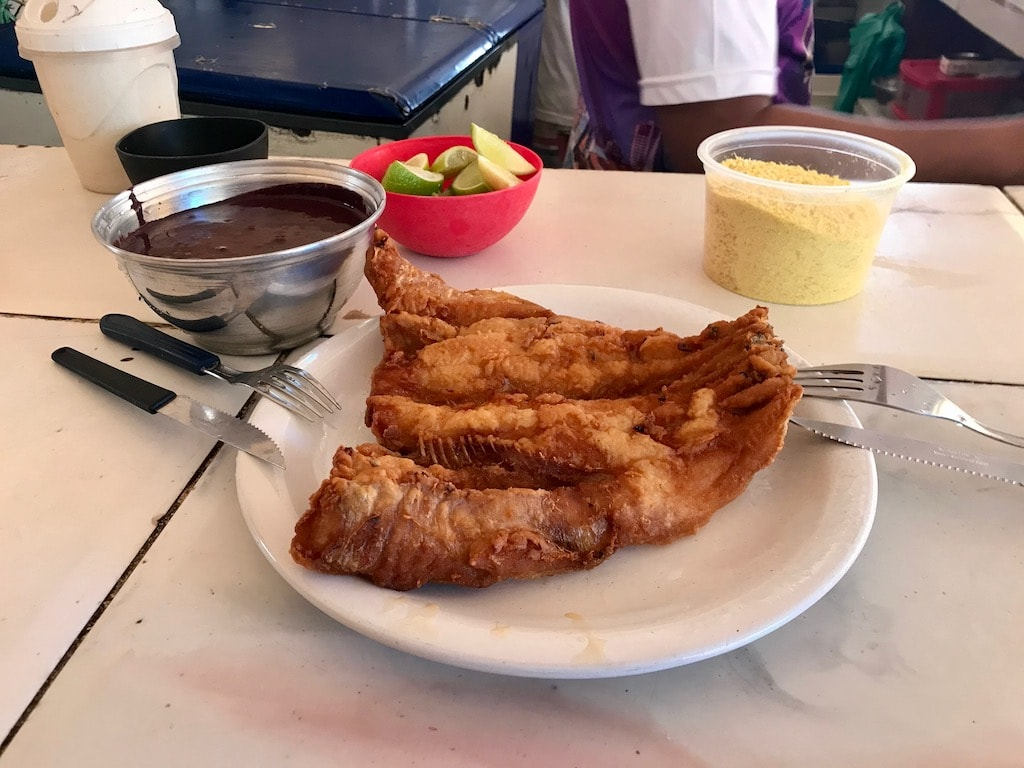 Un piatto di pesce fritto, una ciotola di açai e la farofa