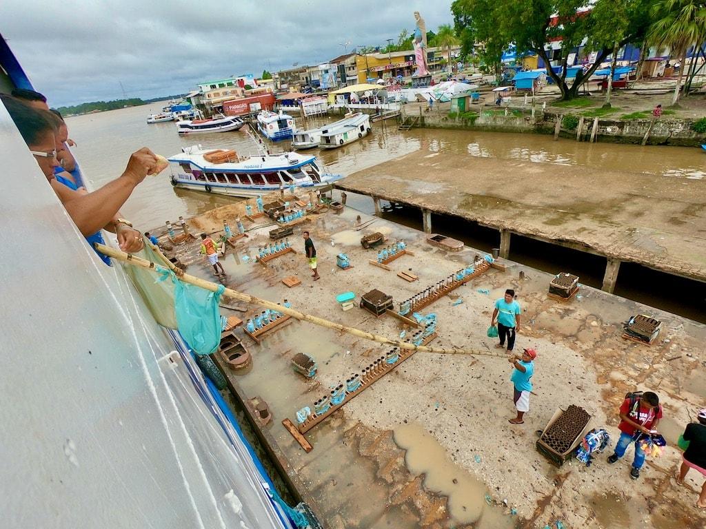 Venditori fanno arrivare il cibo ai clienti sulla barca tramite lunghi pali di bamboo